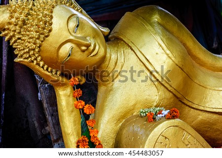 Golden reclining Buddha with flower garland offering at Buddhist temple, Vientiane, Laos - stock photo