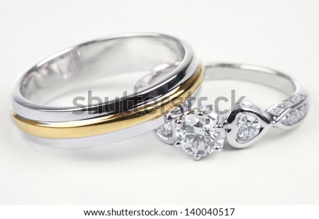 Golden ring and contemporary diamond ring, Isolated on white background. - stock photo