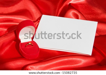 Golden ring in jewerly  box  and empty card on red satin - stock photo