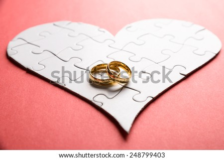 Golden Rings On Heart Made Of Puzzle Over Orange Background - stock photo