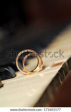 golden rings on white piano key - stock photo
