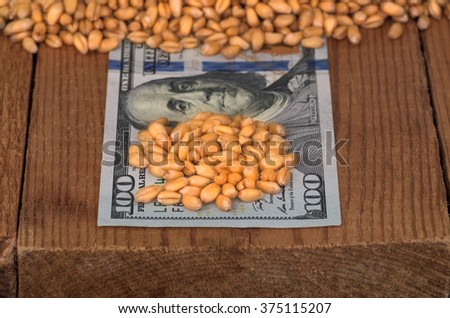 Golden ripe organic wheat on dollar bills - stock photo