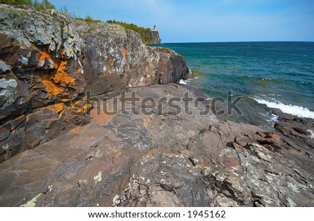 Golden rock wall under Split Rock Light House on Lake Superior. More with keyword Series14  - stock photo