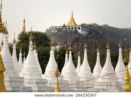 Golden Sandamuni Pagoda with row of white pagodas. Amazing architecture of Buddhist Temples at Mandalay, Burma - stock photo