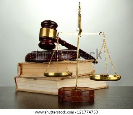 Golden scales of justice, gavel and books on grey background - stock photo