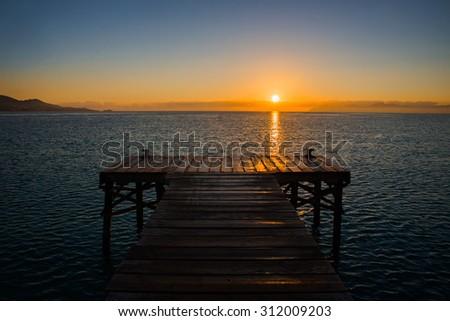 Golden sea sunset on the wooden pier. Spain, Mallorca. - stock photo