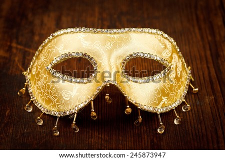 Golden shiny Venice mask on rustic wooden background - stock photo