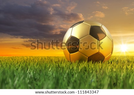 Golden Soccerball 3D on playing field under beautiful sundown - stock photo