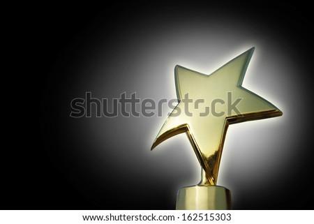 Golden star award against gradient black background - stock photo