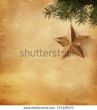Golden star  hanging on a spruce on paper  background - stock photo