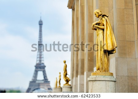 Golden statues and Eiffel tower on square in Paris - stock photo