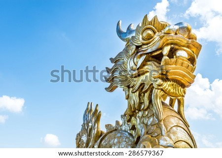 Golden stone dragon statue in Vietnam with face close-up on blue sky background. Leftside view. Symbol of vietnamese mythology and folklore. Religion, culture and art of Asia. - stock photo