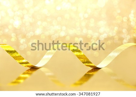 Golden Streamer on shiny background. Holiday background or greeting card. Selective focus - stock photo