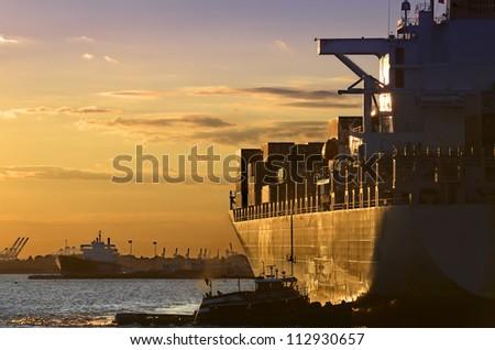 Golden sun beams lighten a cargo-ship in Manhattan Bay - stock photo