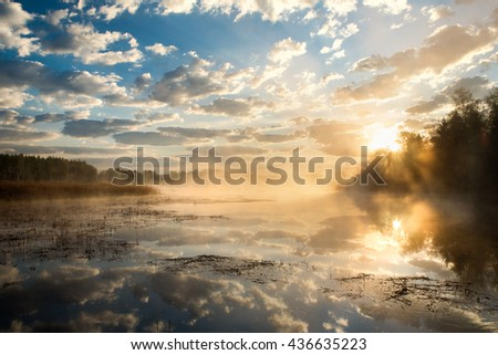 golden sun rises over the river and a fog creeps  water, the rays make their way through the trees, a beautiful reflection in the water of the sky and clouds - stock photo