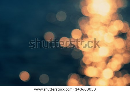 Golden sunlights on blue water background. - stock photo