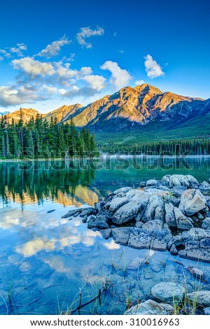 Golden sunrise over Pyramid Mountain at Pyramid Lake in Jasper National Park, Alberta, Canada.  - stock photo