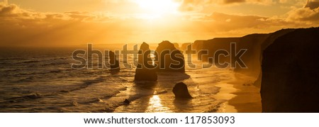 Golden sunset at 12 Apostles rock formation in Victoria, Australia. Dusk sun setting behind the backlit apostles with sea fog rolling in to the cliff face. - stock photo