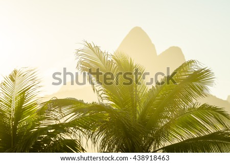 Golden sunset lens flare lights up the silhouettes palm trees against the iconic outline of Two Brothers Mountain in Ipanema Beach, Rio de Janeiro, Brazil  - stock photo