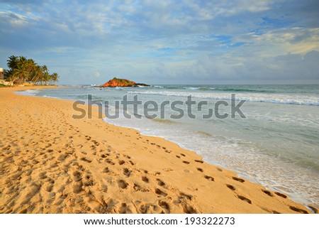Golden sunset on the tropical desert beach of Mirissa, Southern Sri Lanka, during monsoon time. - stock photo