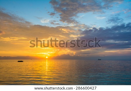 Golden sunset over a turquoise blue ocean in Maldives - stock photo