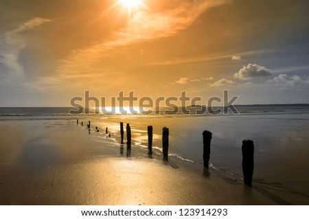 golden sunshine over the beach breakers in Youghal county Cork Ireland on a summers day - stock photo