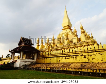 Golden temple in Laos under cloudy sky. - stock photo