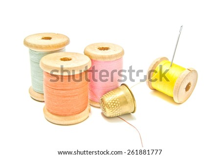 golden thimble and four spools of thread on white - stock photo