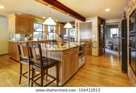 Golden warm wood kitchen with large island and back appliances. - stock photo