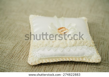golden wedding rings on small white cushion. an image of wedding rings on the pillow - stock photo