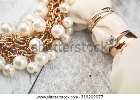 Golden wedding rings on white wood background - stock photo