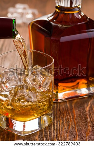 Golden Whiskey Being Poured with Fine Crystal Whiskey Bottle - stock photo