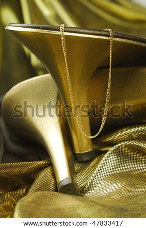 golden womans shoes and jewellery on golden fabric - stock photo