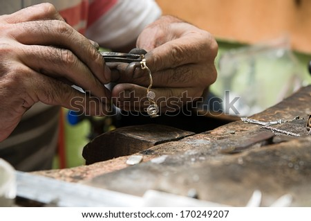Goldsmith working on a silver necklace with his aged hands - stock photo