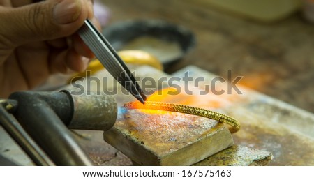 Goldsmith working with a unfinished work - stock photo