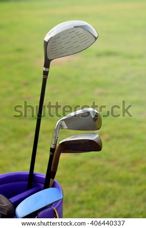 Golf ball and golf club in bag on green grass - stock photo