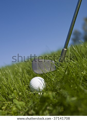 Golf ball and golf club in green gras - stock photo