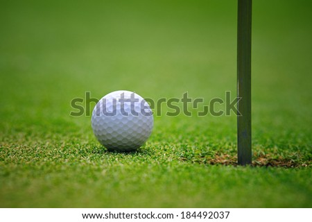 Golf ball and hole - stock photo