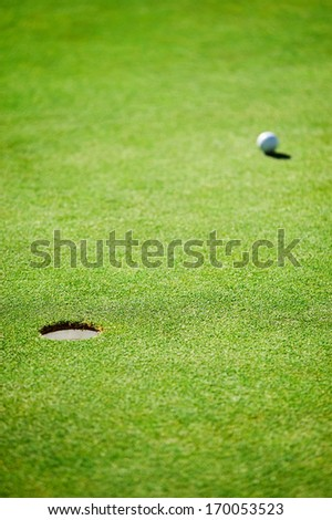 golf ball and hole on green heading towards the cup - stock photo