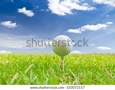 golf ball and tee grass against blue sky - stock photo