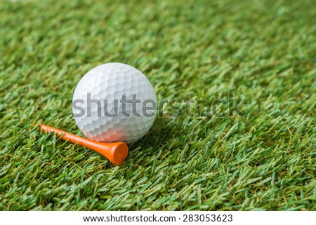 golf ball and wood tee on grass - stock photo