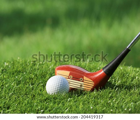 Golf ball and Wooden Driver on green grass background - stock photo