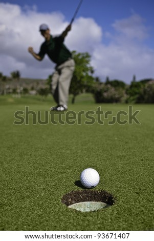 Golf ball approaches hole on the putting green as golfer celebrates in the background. - stock photo