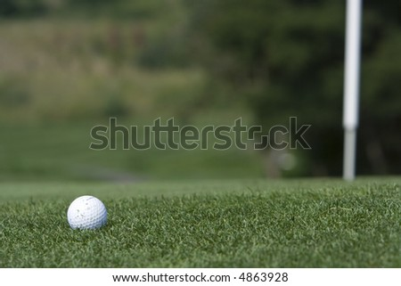 Golf Ball approaching the pin - stock photo