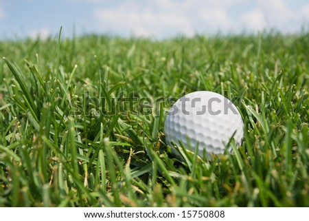 Golf Ball in Fairway Grass against blue sky and clouds. - stock photo