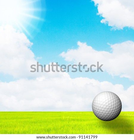 golf ball in green grass on a blue sky and sun - stock photo