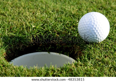 Golf ball is going to fall in hole - stock photo