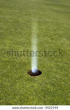 Golf Ball Landing Straight in the hole On a golf green ( hole in one) - stock photo