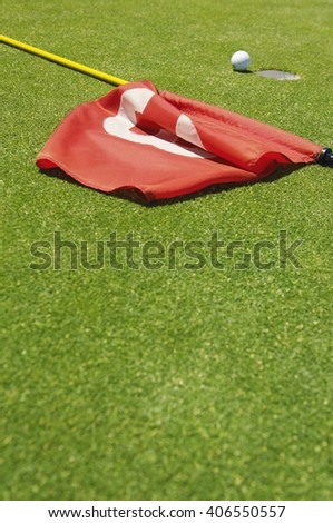 Golf ball near golf hole and a red flag with number 3 on it on the gorund - stock photo