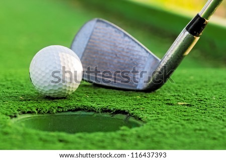 Golf ball near the hole on the green court. - stock photo